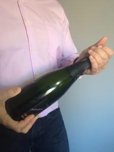 Imagen. La mano Izquierda la deslizamos hacia arriba y procedemos a quitar el capuchón. Abrir una botella de champagne o cava.