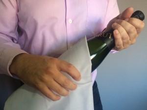 Imagen. Secar la botella con un lito. Abrir una botella de champagne o cava.
